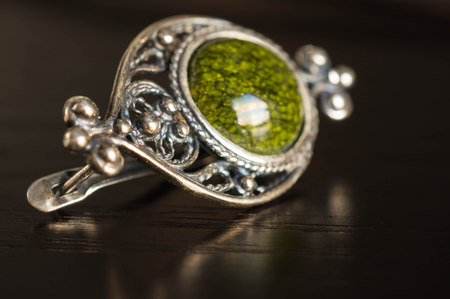 Earring in old style with green stone close up Stock Photo - 24462957