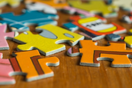 Childrens puzzle scattered on a wooden table close up