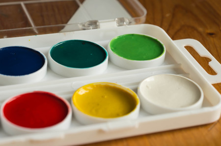 Box with water color paints of different color on a wooden surface photo
