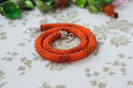 Necklace from bright orange beads on a textile background photo