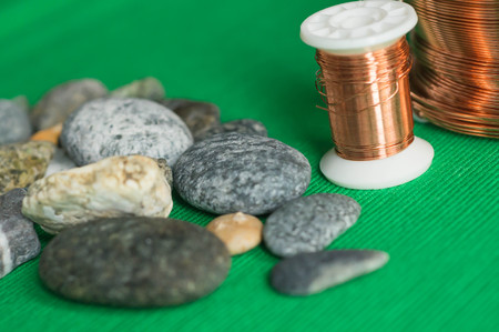 copper wire: Stones and copper wire on a textile background Stock Photo