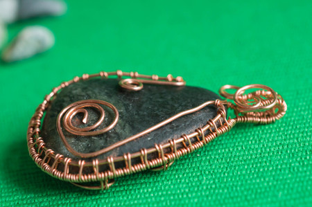 pendent: Pendent from the stone braided by a copper wire close up