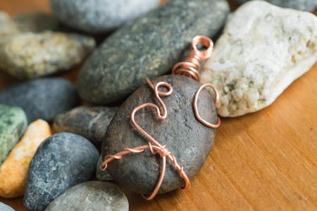 pendent: Pendent from the stone braided by a copper wire among stones