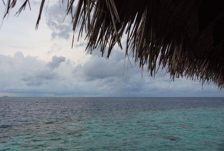 hojas secas: Vista al mar desde debajo de un techo de palma Foto de archivo