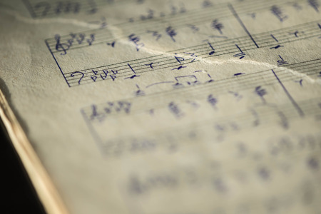 letras musicales: Torn page notebook with handwritten notes for piano