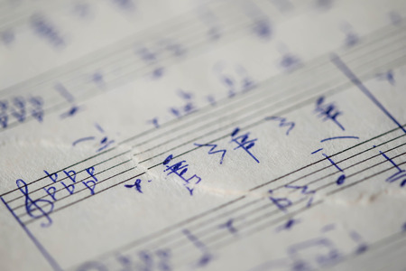music lyrics: Torn page notebook with handwritten notes for piano