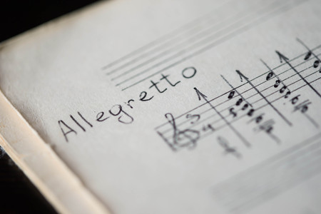 tempo: Musical tempo Allegretto in a music book with hand-written notes