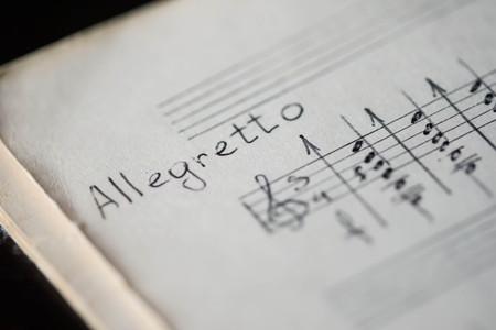 """chiave di violino: Tempo musicale """"Allegretto"""" in un libro di musica con le note scritte a mano Archivio Fotografico"""