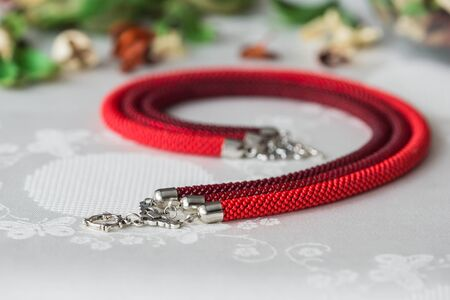 beaded: Beaded necklace of red color from three ropes Stock Photo