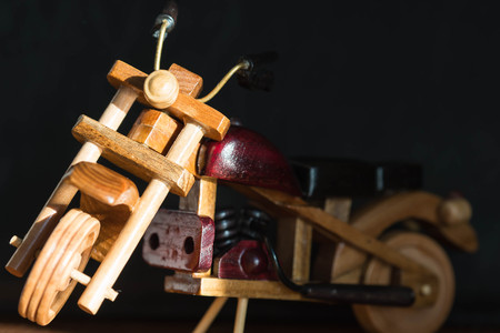 wooden toy: Wooden toy motorcycle on a dark background