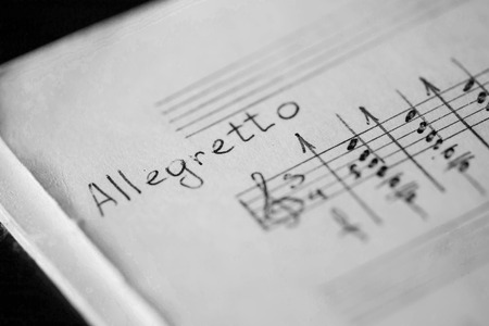 tempo: Musical tempo Allegretto in a music book with hand-written notes. Black and white