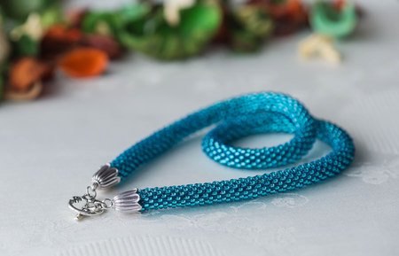 beaded: Turquoise beaded crochet necklace on textile background
