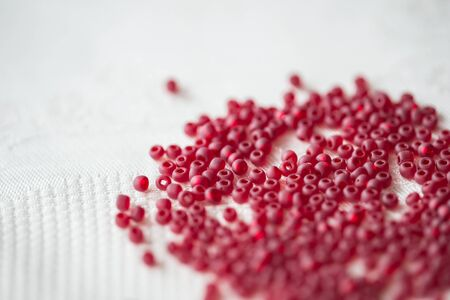 seed beads: Seed beads of red color on the textile background close up