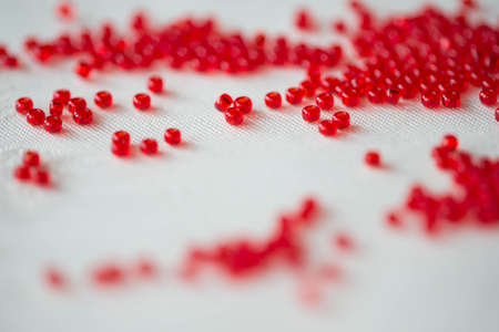 seed beads: Seed beads of dark red color on the textile background close up