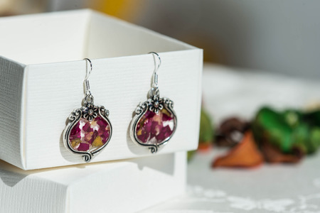 Earrings made of epoxy resin and natural rose petals close up