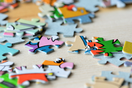 Childrens puzzles on a wooden background close up
