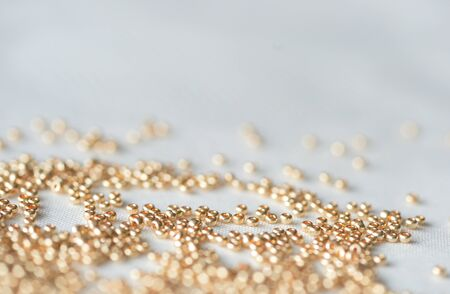 seed beads: Seed beads of golden color on the textile background Stock Photo