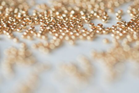 Seed beads of golden color on the textile background Stock Photo
