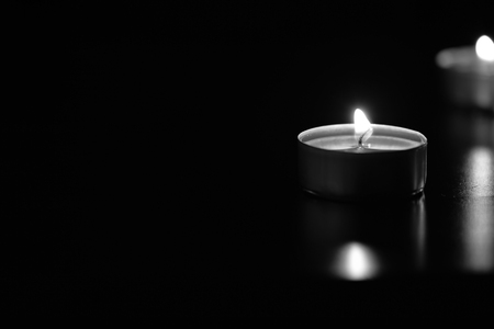 tranquillity: Some burning candles in the dark, black and white