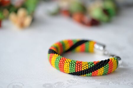 Colorful beaded crocheted bracelet on textile background