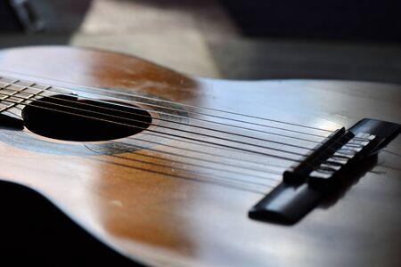 music lyrics: The old guitar and music books illuminated by the sun Foto de archivo