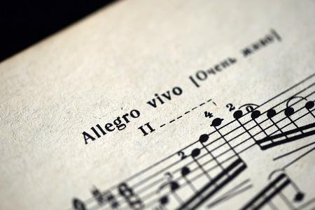 allegro: Musical tempo Allegro vivo in a music notebook close up Stock Photo