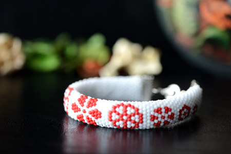 Handmade beaded bracelet with floral print on a dark background