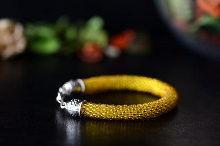 Yellow beaded bracelet on a dark background closeup Stock Photo
