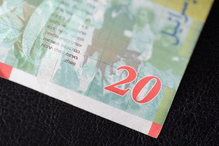israeli: Twenty Israeli shekels on a dark background