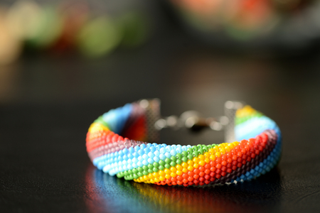 Bead crocheted bracelet of a rainbow colors on a dark background