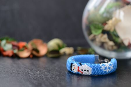 Blue Christmas bracelet with image of snowman on a dark background