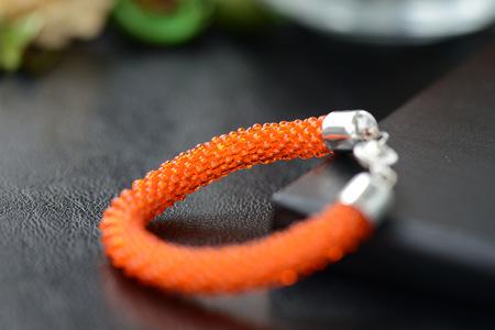 smooth: Orange color beaded bracelet on a dark background