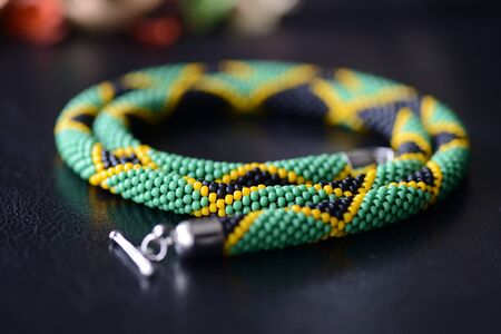 Beaded necklace in the colors of the flag of Jamaica on a dark background