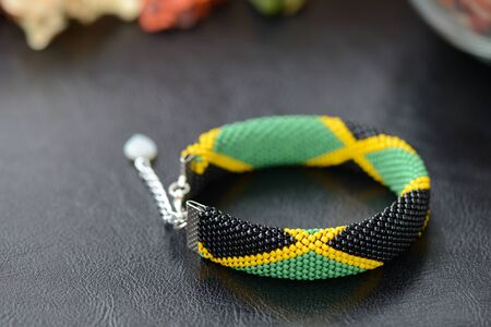 Bead crochet bracelet in the colors of the flag of Jamaica on a dark background