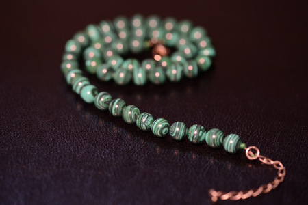 Green necklace of beads of malachite close up