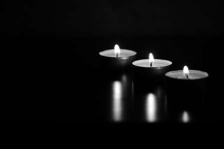 Burning candles in the dark. Black and white