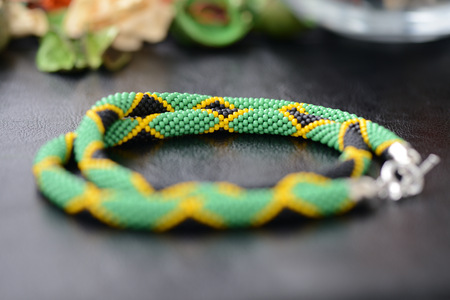 Necklace in colors of Jamaican flag on a dark background close up