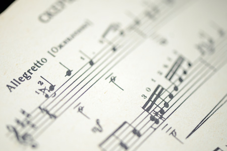 Musical tempo Allegretto in an old music notebook close up