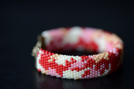 Red camouflage seed beads bracelet on a dark background close up Stock Photo