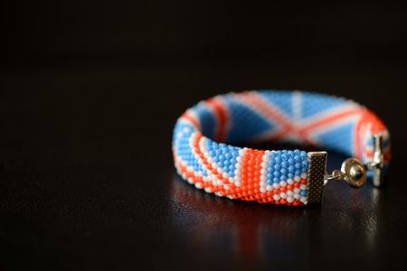 Beaded bracelet British flag on a dark background close up