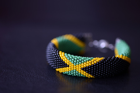 Seed beads bracelet Jamaican flag on a dark background close up