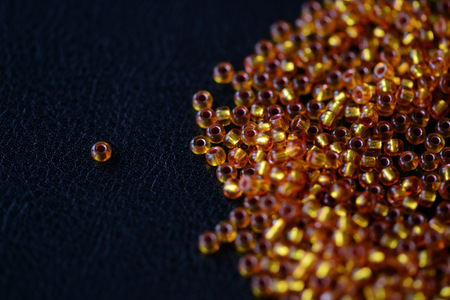 Round yellow seed beads scattered on a dark surface close up