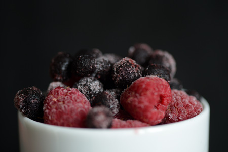Frozen raspberries and blueberries on a dark background close up