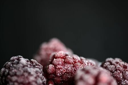 Blackberry berries covered with hoarfrost on a dark background close up Stok Fotoğraf