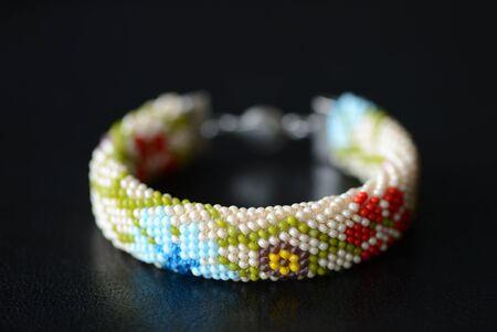 Beige bracelet with floral print on a dark background close up