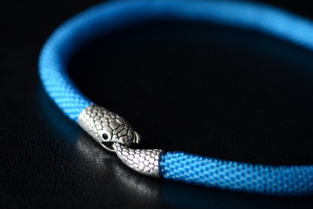 Blue beaded necklace with snake head lock on a dark background close up Stock Photo