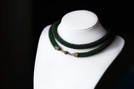 Bead crochet necklace green color on a dark background close up