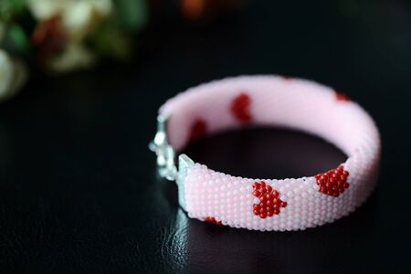 Pink beaded bracelet with images of red hearts on a dark background close up