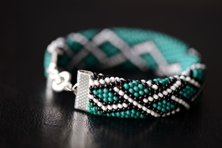 Green bead crochet bracelet with celtic print on a dark background close up Stock Photo
