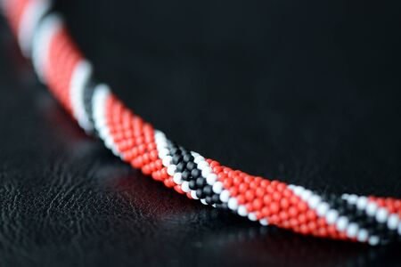Bright beaded necklace red, black and white colors on a dark background close up Stock Photo